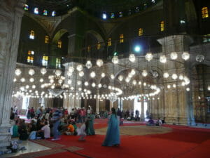Inside a mosque, people wearing blue sheets